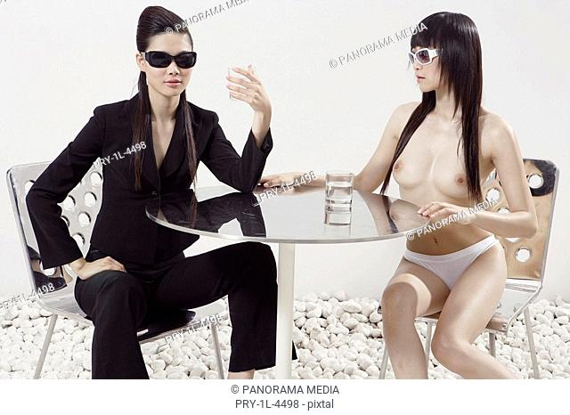 Young woman sitting with naked woman, holding glass of water