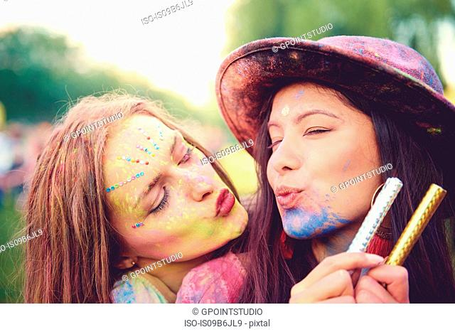 Portrait of two young women covered in coloured chalk powder puckering lips at festival