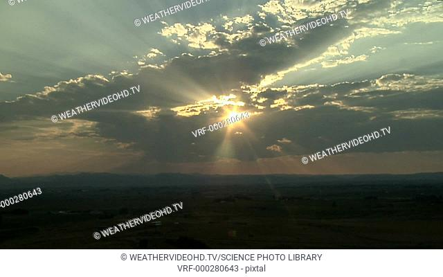 Crepuscular rays shining through altocumulus clouds. Although the rays appear to diverge, they are in fact parallel, and their appearance is a trick of...