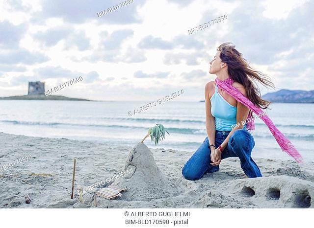 Caucasian woman building sandcastle on beach