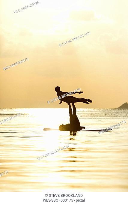 Thailand, couple doing yoga on paddleboard at sunset