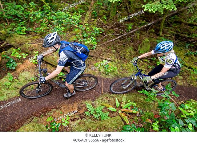 A pair of mountain bikers make their way up a trail in Powell river, upper Sunshine coast of the Vancouver coast and mountain range, British Columbia, Canada