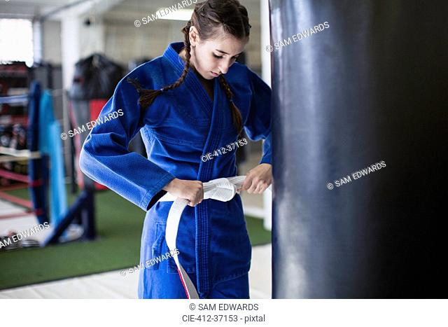 Young woman tightening judo belt at punching bag in gym