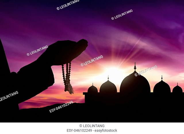 Image of silhouette man praying with sunset background