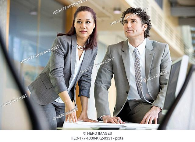 Businessman and businesswoman looking away while working at desk in office