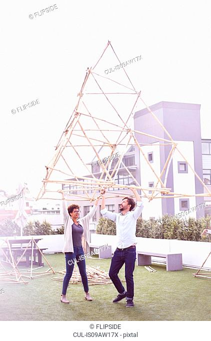 Couple arms raised, carrying wooden structure