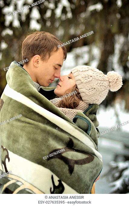 Handsome man kiss on the forehead her beloved, beautiful, pretty, attractive girl with sweater, mittens, winter, cold, snow forest, hut, love, happy