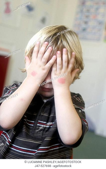 3 year old boy  at nursery, hiding his face with his hands