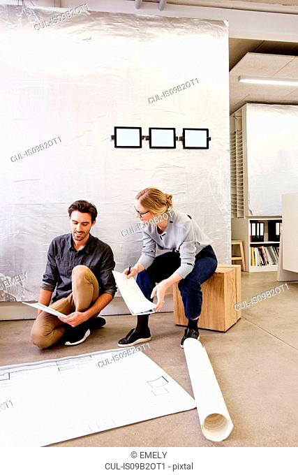 Architects in office discussing blueprints