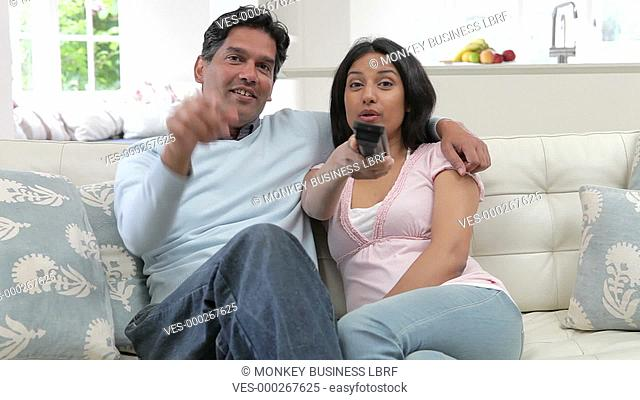Asian Indian couple sitting on sofa together watching television.Shot on Canon 5d Mk2 with a frame rate of 25fps