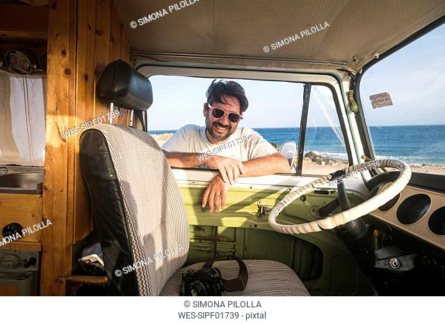Spain, Tenerife, portrait of laughing man leaning on car window looking inside