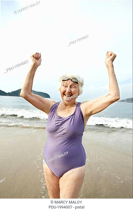 Elderly woman in swimsuit and goggles on beach