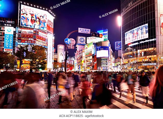 Crowd of people crossing the busiest in the world Shibuya interesection lit with street lights and colorful signs at night