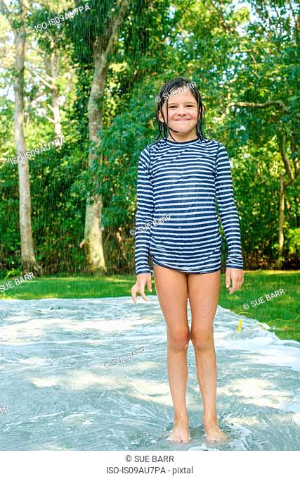 Portrait of young girl standing on slip n slide water mat in garden