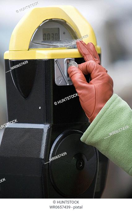 Close-up of a persons hand inserting a coin into a parking meter