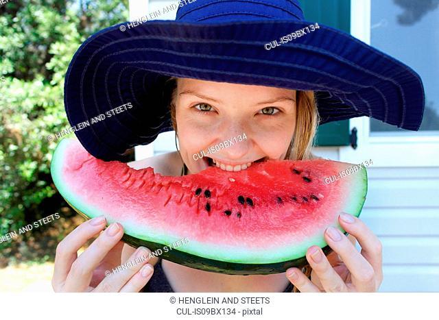 Woman biting into watermelon