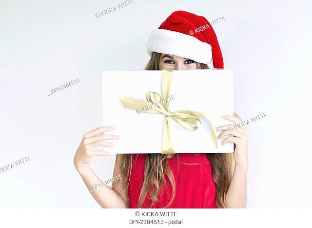 A girl dressed in a red shirt and santa hat holds a wrapped gift; Hawaii, United States of America