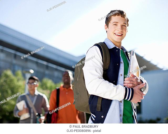 Student carrying folders outdoors