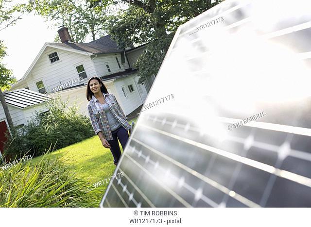 A woman walking towards a solar panel in a farmhouse garden