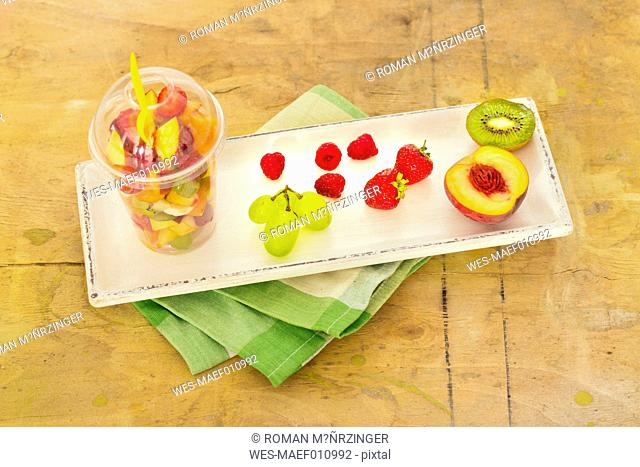 Plastic cup of fruit salad and fruits on wooden tray