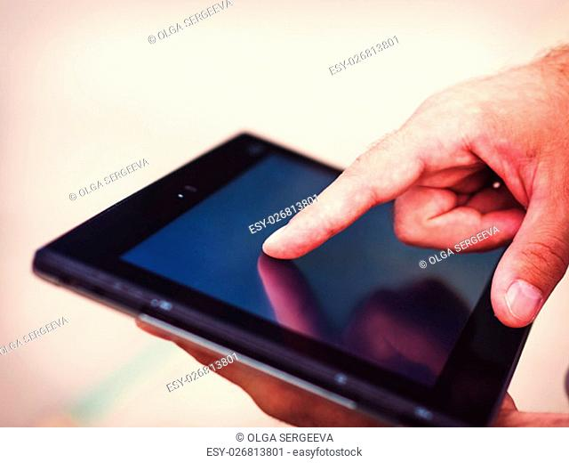 Smart casual man with digital tablet outdoors, close up. Focus on finger. Modern remote work concept