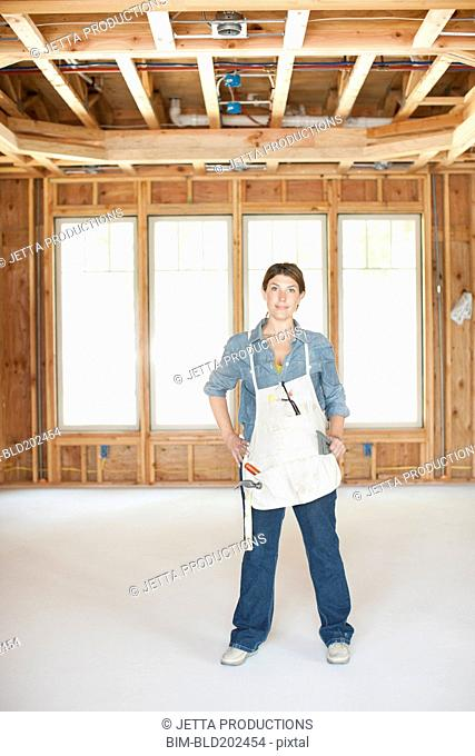 Caucasian construction worker standing in unfinished room