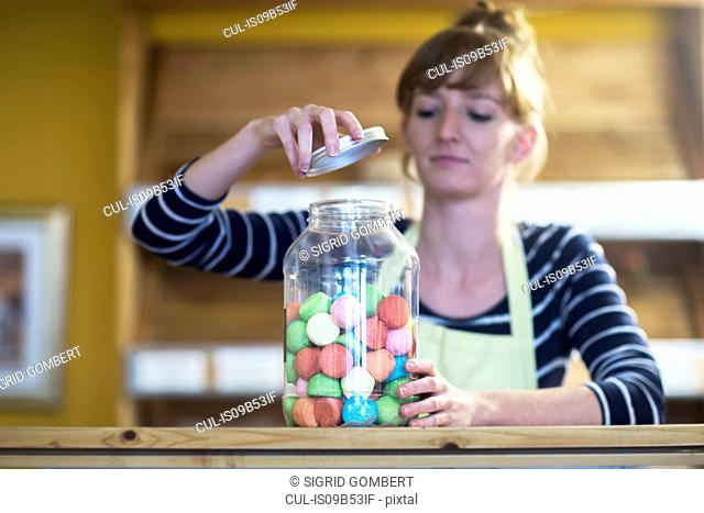 Young woman in food shop, opening jar of sweet food
