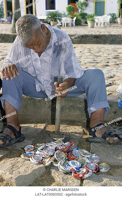 Ilha/ Isla Grande. Man seated flattening aluminium cans with hammer. For sale