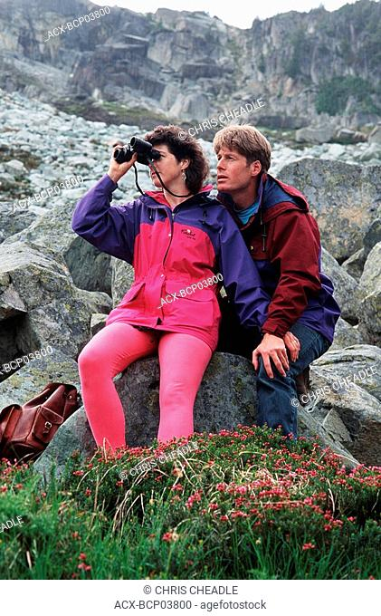 couple with binoculars in mountains with heather foreground, Whistler, British Columbia, Canada