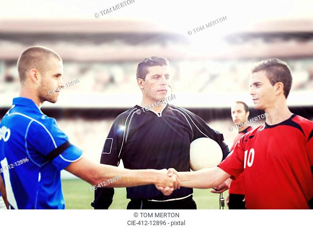 Soccer players shaking hands on field