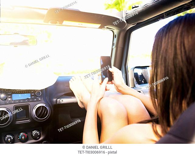 Young woman sitting in car with legs on dashboard using smart phone