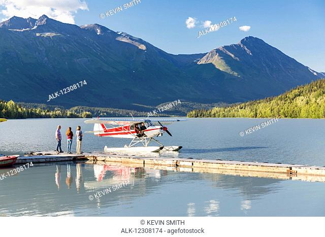 Visitors wait for the pilot to dock while, Trail Lake Float Plane Base, Moose Pass, Kenai Peninsula, Southcentral Alaska, USA