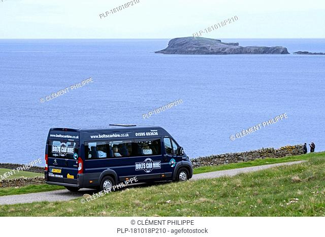 Group tourists driving along desolate coastal road in rented van / hired van from the Bolts Car Hire company in Shetland, Scotland, UK