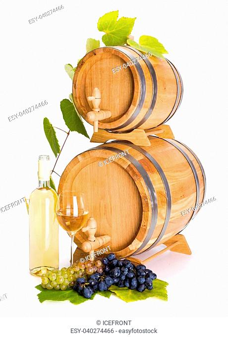 White wine in front of stacked barrels, grape clusters and leaves