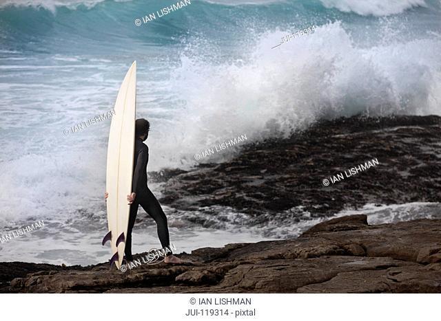 Surfer with surfboard wearing wetsuit watching ocean waves crash over rocks