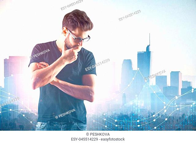 Portrait of casual thoughtful young man on abstract city background with glowing forex chart and daylight. Statistics and finance concept