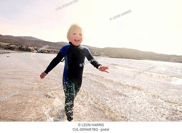 Boy running on beach, Loch Eishort, Isle of Skye, Hebrides, Scotland