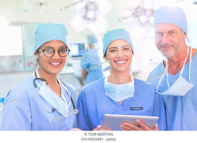 Portrait smiling, confident surgeons using digital tablet in operating room