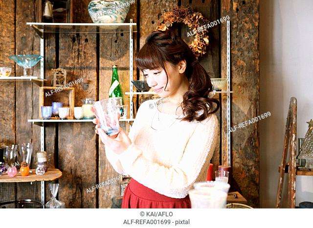 Young Japanese woman enjoying visit to glass workshop in Kawagoe, Japan