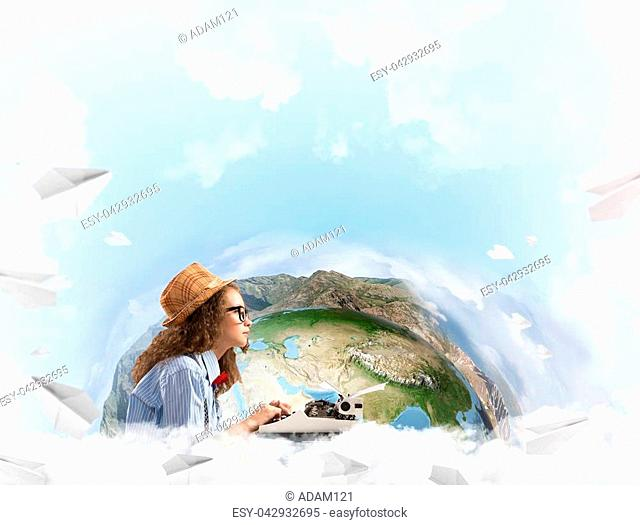 Portrait of woman writer looking away and using typing machine while sitting at the table with flying paper planes and Earth globe among cloudy skyscape on...