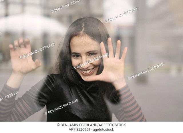 portrait of playful woman behind glass window, in Munich, Germany