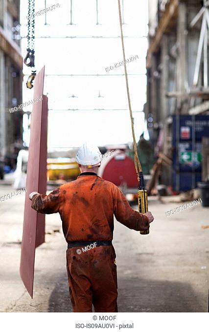 Rear view of worker using winch in shipyard workshop