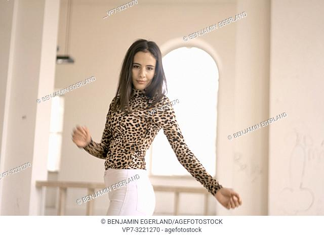 woman dancing indoors, fashionable clothing style, movement, in Munich, Germany