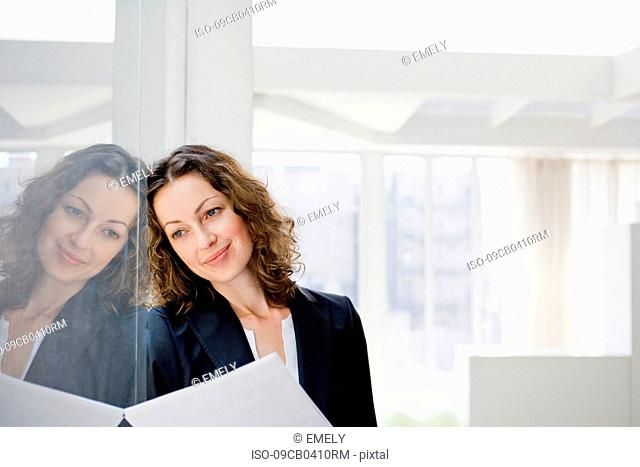 Businesswoman leaning at glass window