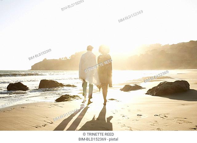 Back lit couple wrapped in blankets walking on beach