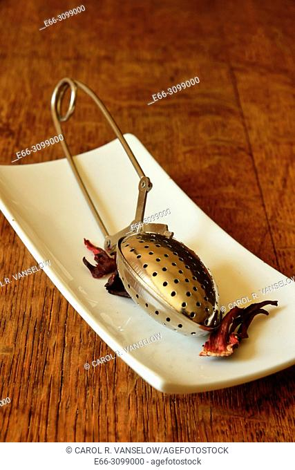 teaspoon tea strainer with hibiscus tea, on white plate