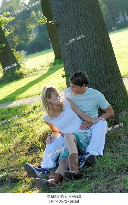 Young couple lying under trees