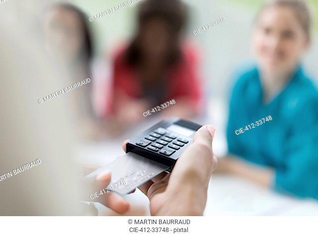Close up waitress using credit card reader at cafe table