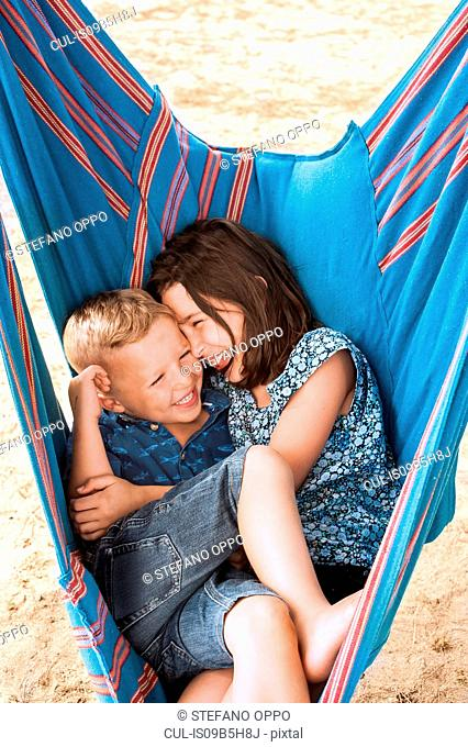 Girl and brother laughing huddled in hammock on Poetto beach, Cagliari, Italy