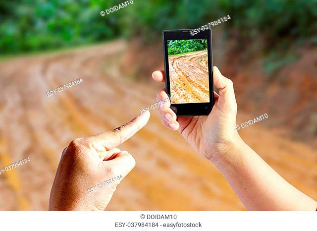 Business conceptual- Focused on right hand holding empty mobile with Trekking road mud blurred background